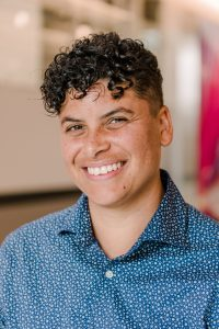 Image of Chris Hawn, smiling nonbinary Black person with short curly hair